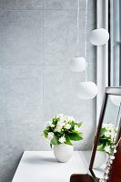 Vase of white flowers and dressing mirror on dressing table below pendant lamps