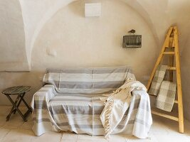 Striped throw on sofa and easel in Apulian trullo
