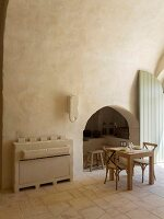 Arched niche and masonry sideboard next to small dining table and chairs in restored Apulian trullo