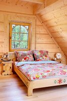 Double bed with floral bed linen in attic room with pale wooden cladding