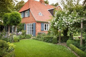 Brick house with shutters in idyllic garden
