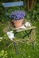 Flowers, seashells and wreath on old folding chair in garden