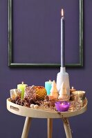 Colourful collection of candles on tray table in front of purple wall