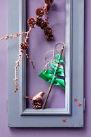 Green ribbons knotted around twig to form small Christmas tree