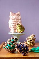 Pine cones wrapped in colourful thread in front of owl ornament