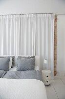 Schlafzimmer in Weiss, Doppelbett mit grauer Bettwäsche und bodenlangem Vorhang am Kopfende