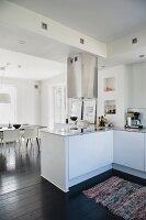 Offene weiße Küche mit Theke und Edelstahl Dunstabzug, im Hintergrund Essplatz