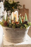 White pillar candle and Christmas decorations arranged in zinc tub