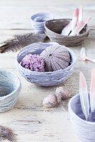 DIY-Schalen aus pastellfarbenem Strickgarn mit Federn, Seeigelgehäuse und Pompon dekorativ arrangiert