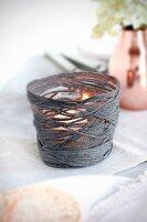 Selbstgebastelte Windlichthülle mit Teelichtglas aus dunkelgrauem Garn
