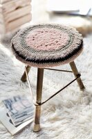 Crocheted seat cushion on three-legged stool on flokati rug