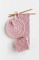 Round crocheted coaster and long piece of knitting in pink yarn