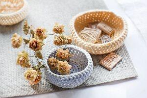 Gehäkelte, pastellfarbene Schälchen dekoriert mit getrockneten Hopfenblüten und Tonbildern