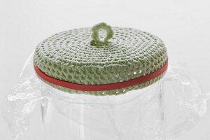 Gehäkelter, eingekleisterter Deckel zur Formgebung mit Gummi auf Glasgefäß mit Frischhaltefolie gespannt