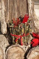 Red candles and berries in plant pot wrapped in twigs