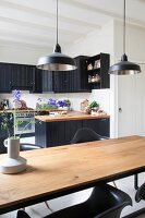 View of black country-house kitchen across wooden table