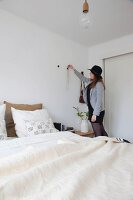 Woman hanging necklace on wall hook in bedroom