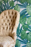 Armchair with gold brocade cover against green leaf-patterned wallpaper