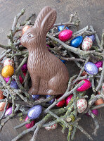 Chocolate Easter bunny in nest of twigs and chocolate eggs