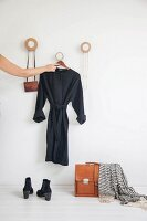 Arm hanging dress on coat pegs made from round wooden discs