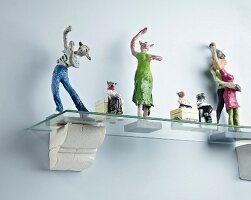 Various figurines on hand-made glass bracket shelf