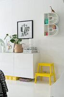 Bright yellow step stool next to sideboard below B-shaped shelving unit