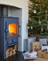Gifts below Christmas tree next to cast iron log burner in fireplace