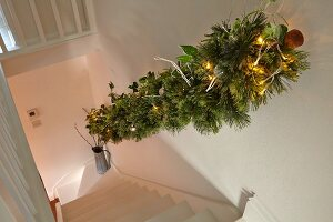 View down staircase with festively decorated handrail in rustic stairwell