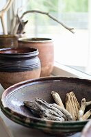 Weathered pieces of wood in ceramic bowl on windowsill
