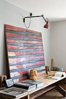 Abstract red and black artwork on rustic wooden table under wall-mounted lamp
