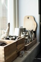 Wooden crates of kitchen utensils on windowsill
