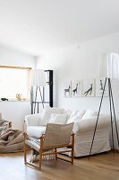 Designer standard lamp next to loose-covered sofa and armchair with wooden frame and linen seat and backrest in white living room