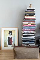 Framed picture of woman next to stacked books and vintage doctor's bag on parquet floor