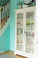 Crockery in vintage display case against turquoise wall next to wooden staircase with storage cupboards below