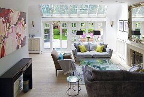 Grey sofa set and open fireplace in living room with terrace doors and glass roof