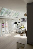 Sofa in sunshine next to terrace windows and glass roof in elegant living room