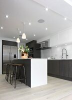 White kitchen counter and bar stools in modern fitted kitchen