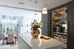 Glossy, white island counter and fitted cupboards with open sliding doors in elegant, open-plan kitchen
