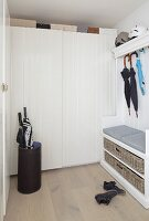 Cloakroom with hat rack, bench, umbrella stand, umbrellas hung from coat rack and white fitted wardrobes