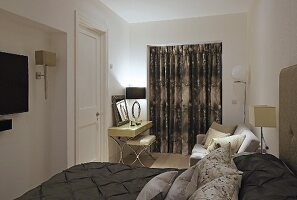 Elegant double bed with dark brown bedspread and arranged scatter cushions and dressing table in front of French windows with closed curtains
