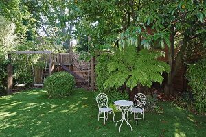 White vintage table and chairs in front of palm trees and tall trees in summery garden with swings in play area in background