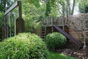 Play area with wooden climbing frame in summery garden