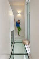 Girl walking down stairs onto landing with glass floor