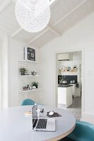 Laptop on round white table in front of String shelves next to open doorway