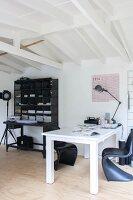 White desk and classic black shell chairs next to black modern bureau