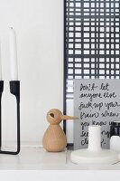 Wooden bird, hand-written card, black candlestick and framed picture on white shelf