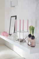 Hyazinthen in Glas, würfelförmiger Kerzenständer mit rosa Kerzen und Papierdeko auf weißer Wandkonsole