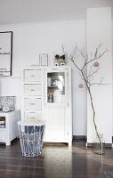 White display cabinet next to bare branch in floor vase decorated with pink paper pompoms