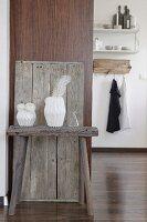 Weisse Papiervasen mit Feder und Ranunkeln dekoriert auf rustikalem Holzbock