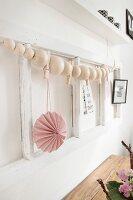 Holzkugelkette an weißem Holzrahmen mit rosafarbenem Papieranhänger